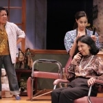 "Ouiser (Karen Huie) ""confronts"" Annelle (Lovelle Liquigan) about church mailings she has been receiving. Seated: Clairee (Dian Kobayashi) in East West Players' ""Steel Magnolias"""